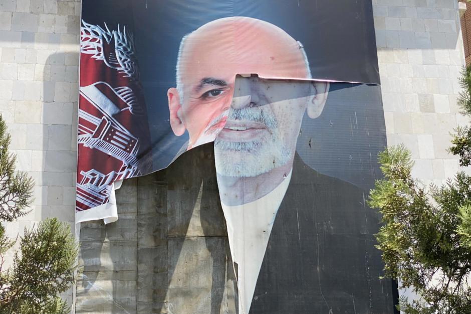 Plakat ze zniszczonym wizerunkiem byłego już prezydenta Afganistanu Ashrafa Ghaniego, który zbiegł z kraju opanowywanego przez talibów tuż przed obchodami 102. rocznicy odzyskania przez Afganistan niepodległości (tj. końca panowania brytyjskiego). EPA/STRINGER Dostawca: PAP/EPA.